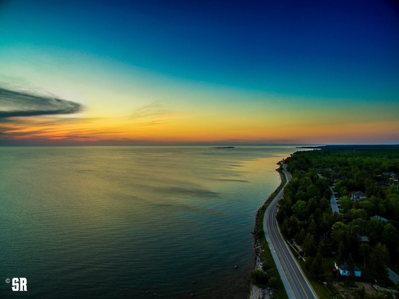 aerial photo of lake huron sunset and winding shoreline road